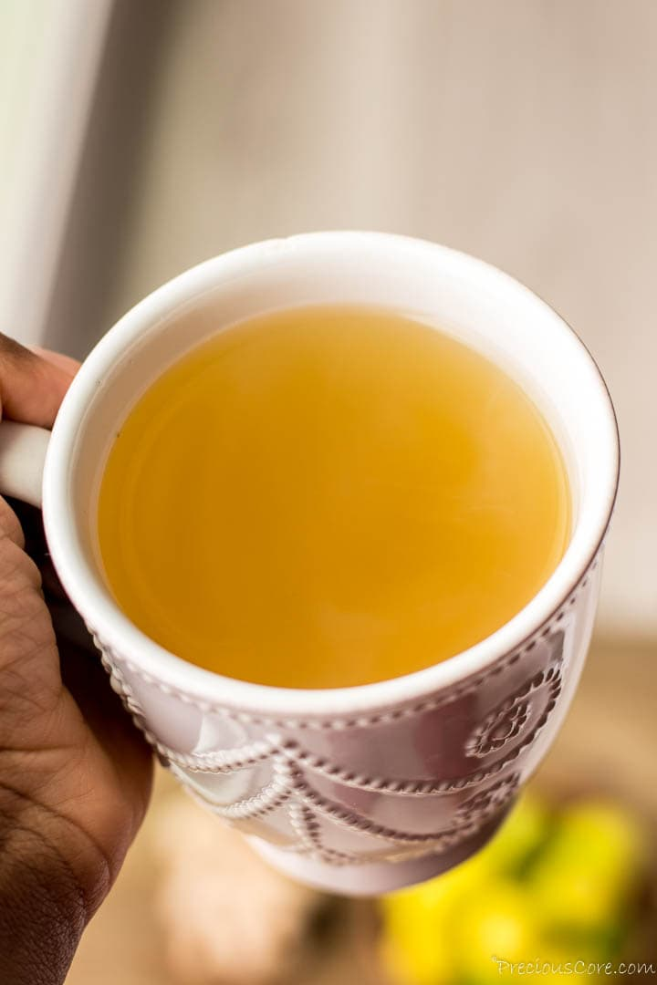 Hand holding a mug of ginger tea