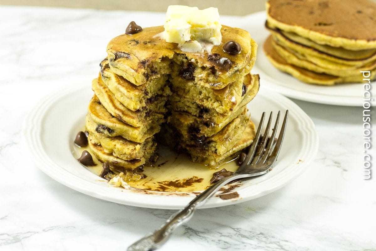 A stack of pumpkin chocolate chip pancakes with maple syrup and chocolate chips. The perfect fall breakfast recipe.