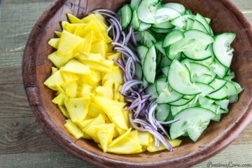 Sliced cucumber, mango and onion in a bowl