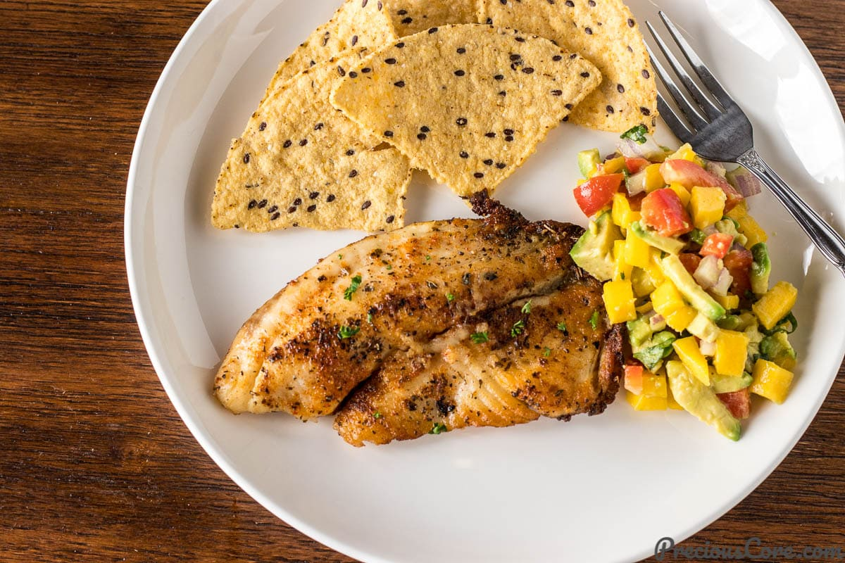 Pan Seared Tilapia on a plate with Mango Avocado Salsa and tortilla chips