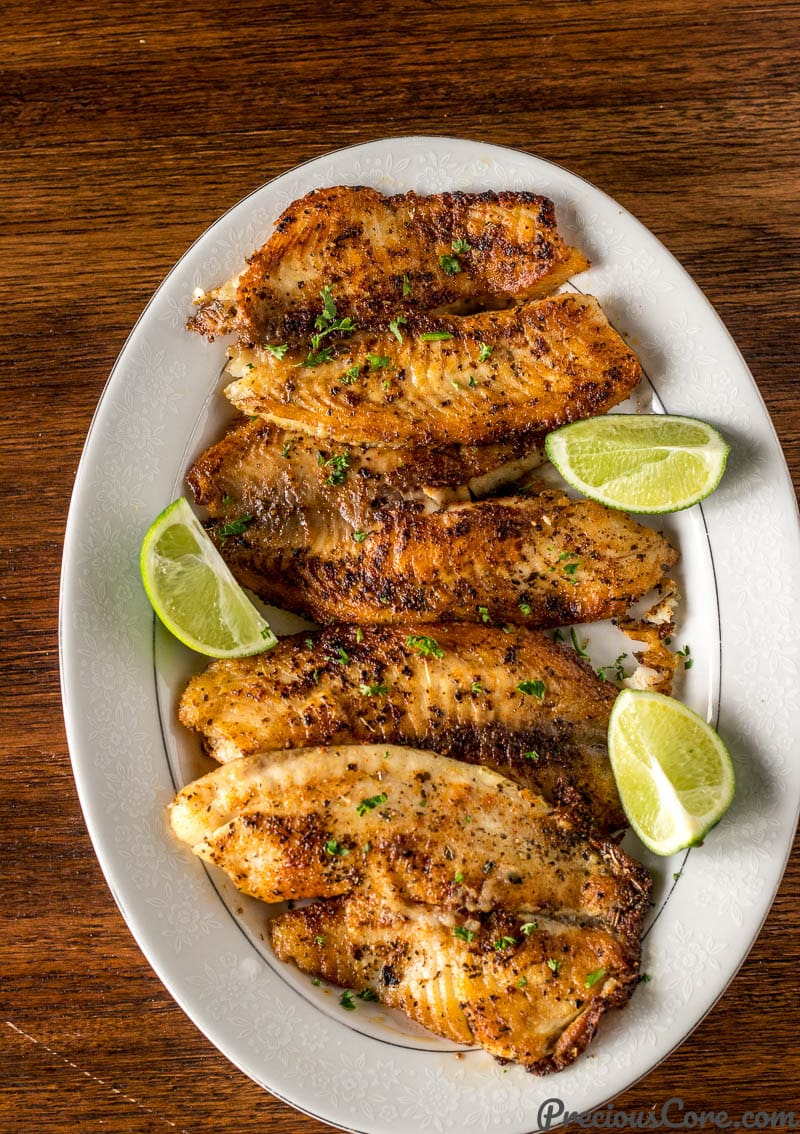 Pan Seared Tilapia on a Serving Tray with lime wedges