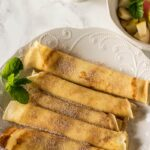 Crepes Served with diced apples and pears in a bowl and coffee