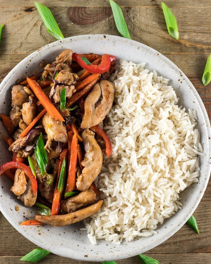 A bowl of rice and chicken stir fry