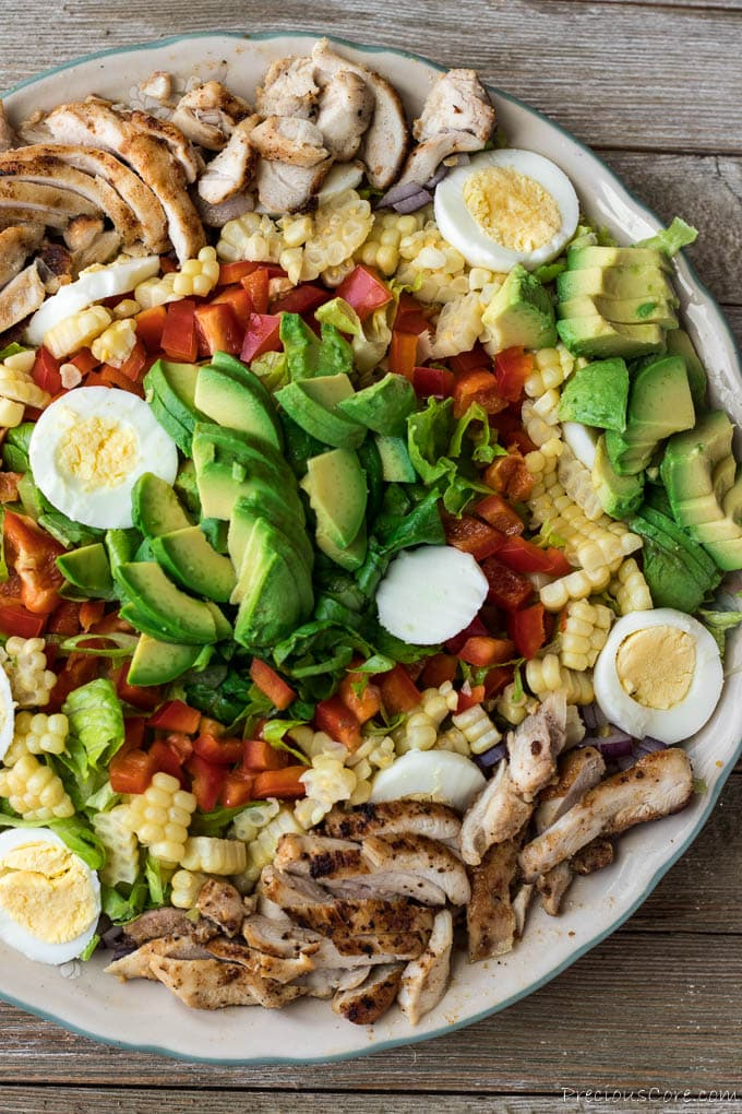 Salad with chicken, eggs, red bell pepper, avocado and romaine lettuce