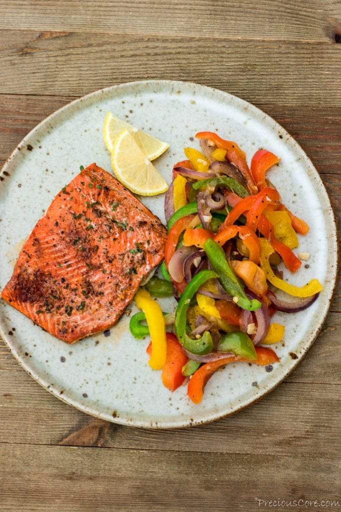 Cajun salmon, sauteed peppers and lemon slices on a plate