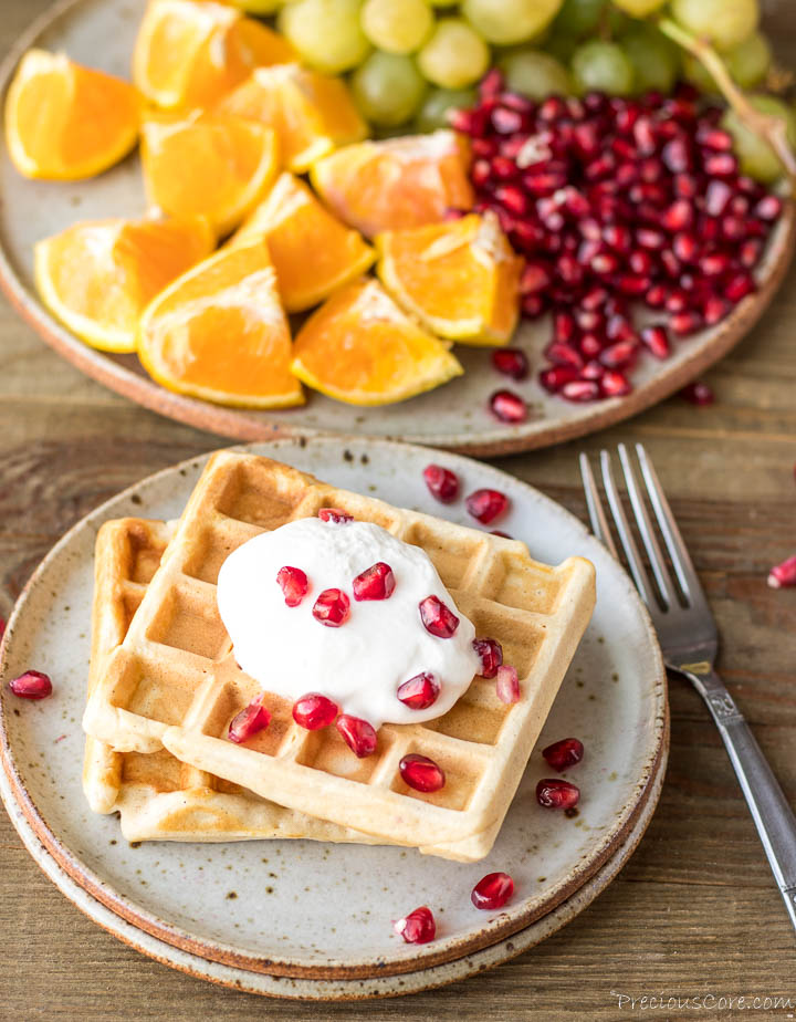 2 waffles on a plate with whipped cream and pomegranate seeds on top