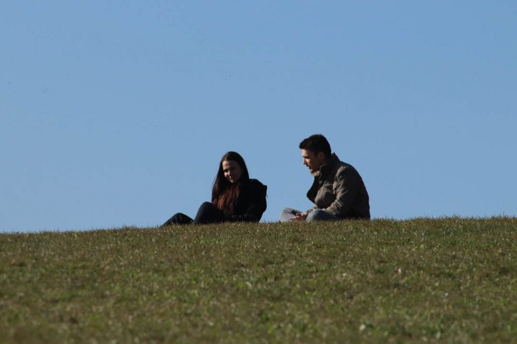 man sitting on grass with woman