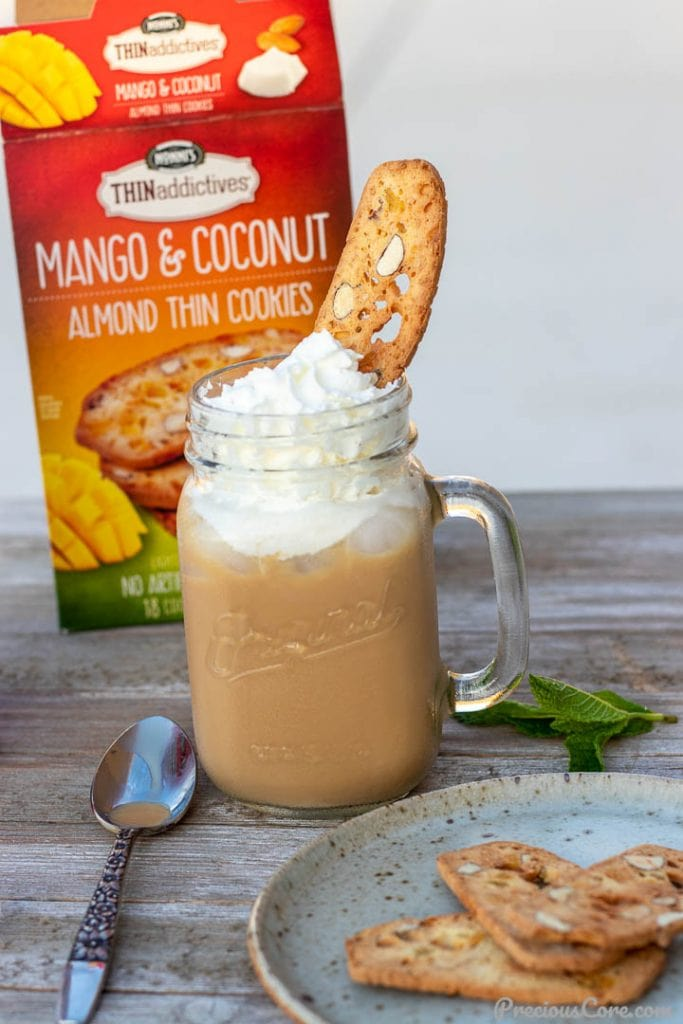 Iced coffee in a mason jar topped with whipped cream and a thin cookie