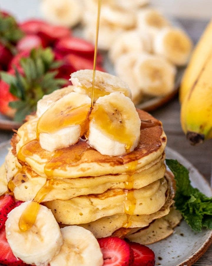 Stack of banana slices on a plate, banan slices on the stack and maple syrup pouring on top