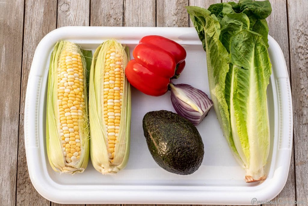 Corn on the cob, avocado, bell pepper, onion and romaine lettuce on a tray