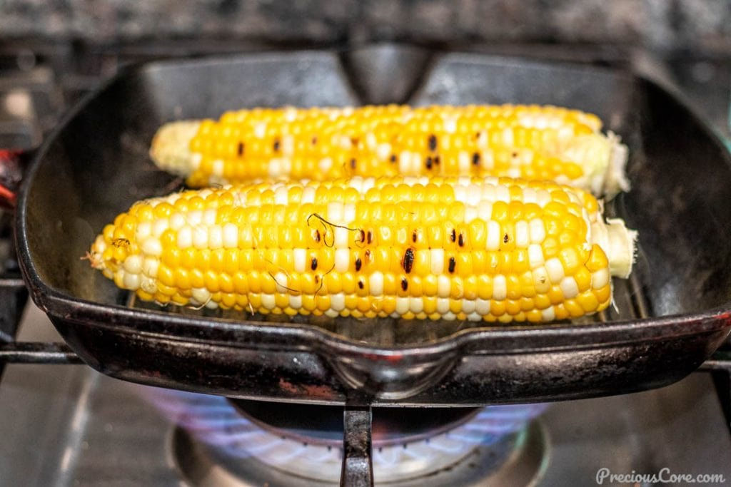 Corn on the cob grilling on grill pan on gas stove