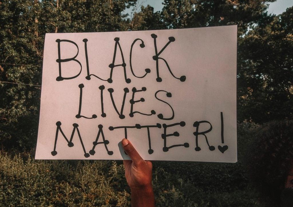 "Black hand holding a ""Black Lives Matter"" placard"
