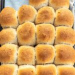 Baked honey whole wheat dinner rolls on a baking sheet lined with parchment paper