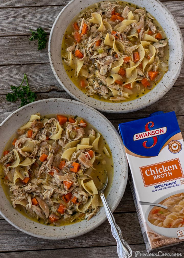 2 bowls of chicken noodle soup with a box of chicken broth on the side.
