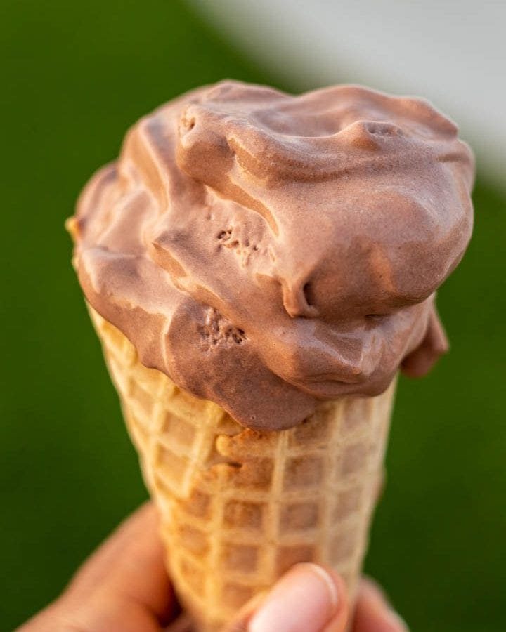 HAND HOLDING CONE OF CHOCOLATE ICE CREAM
