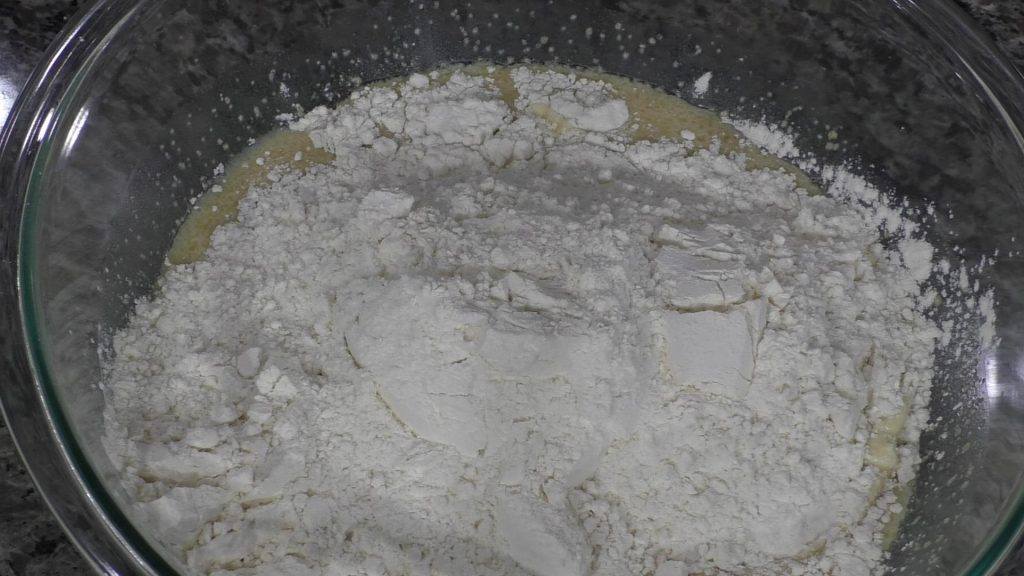 flour in a bowl with wet ingredients for dinner rolls