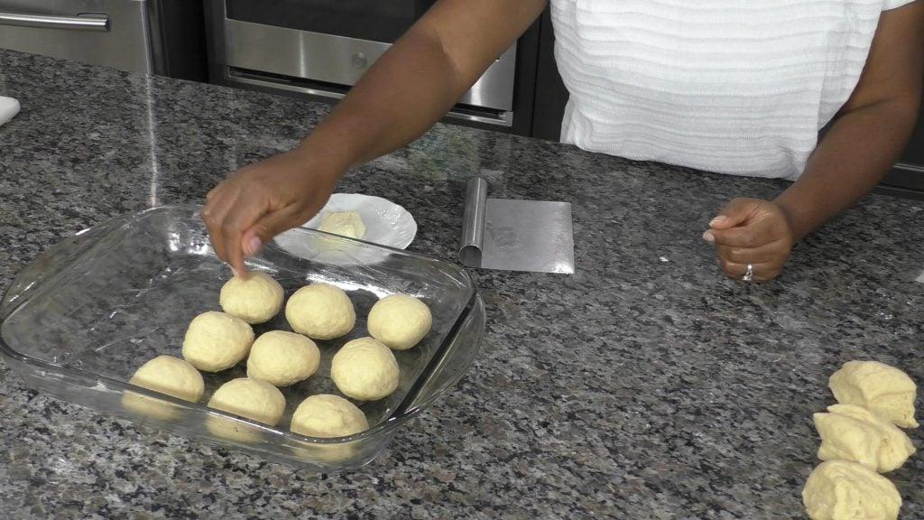 Hand placing balls of dough into a baking dish
