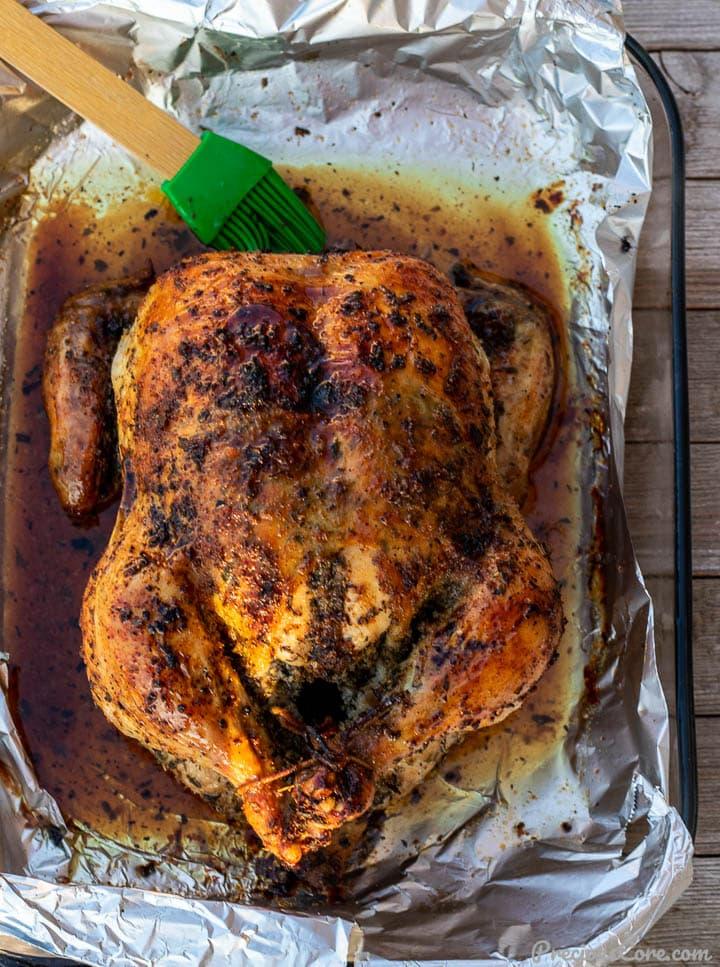 Golden brown roast chicken in baking dish