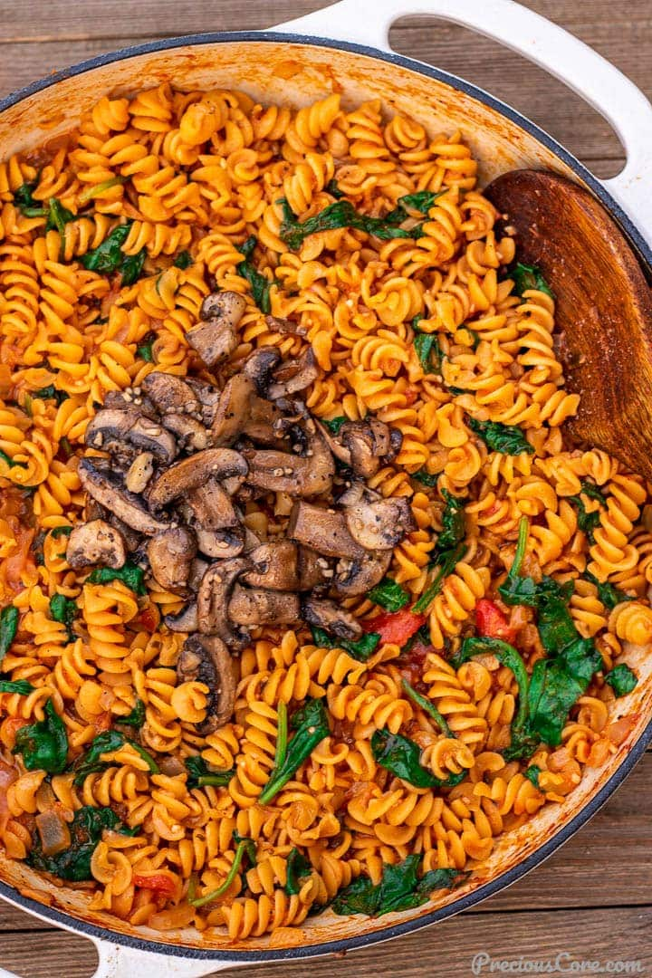 Pot of pasta in red sauce topped with mushrooms