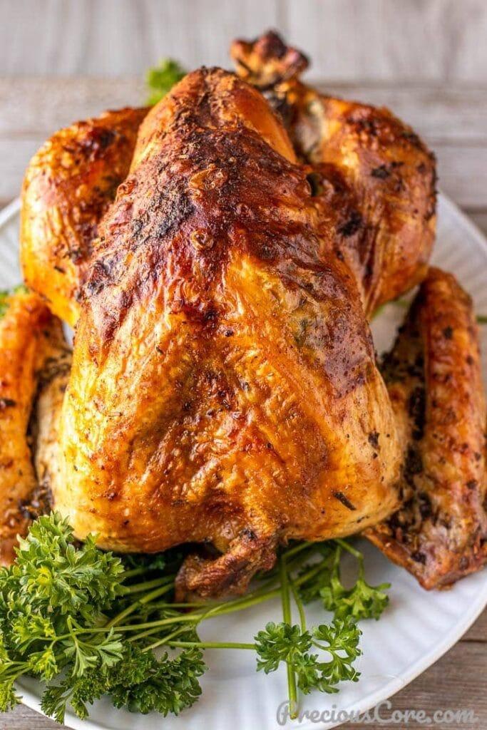 Whole turkey on white platter, garnished with parsley
