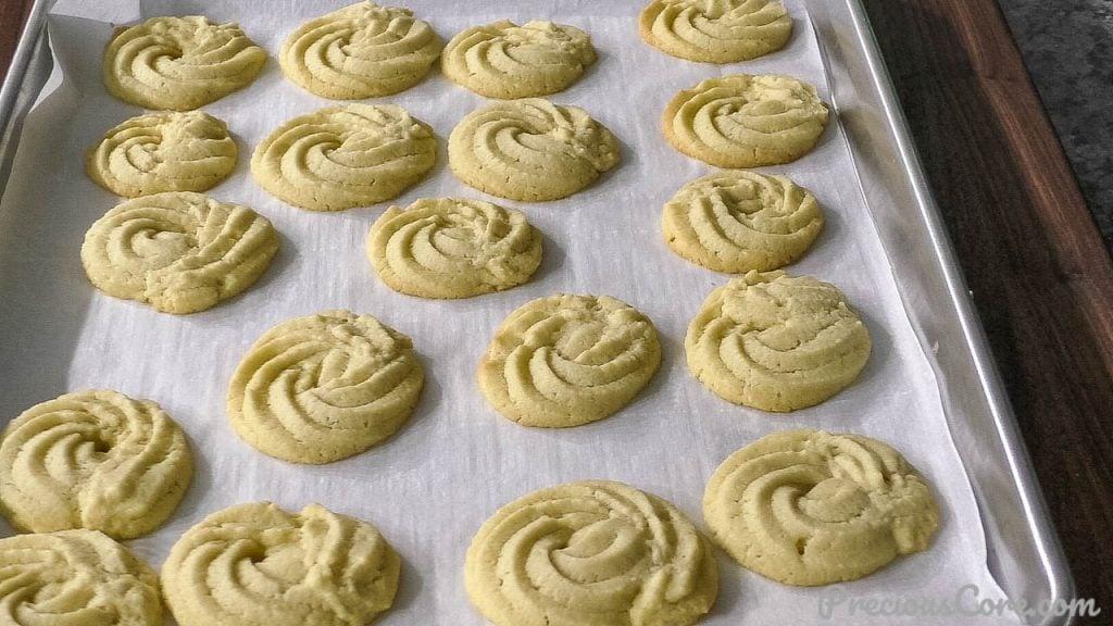 Freshly bakes butter cookies on baking sheet.